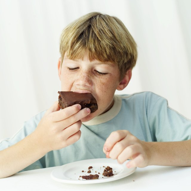 Young boy (12-14) eating a chocolate brownie