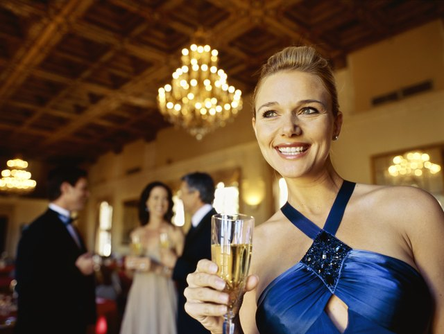 Close up of a mid adult woman holding a champagne flute and smiling