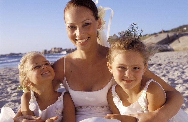 Portrait of bride with flower girls on beach