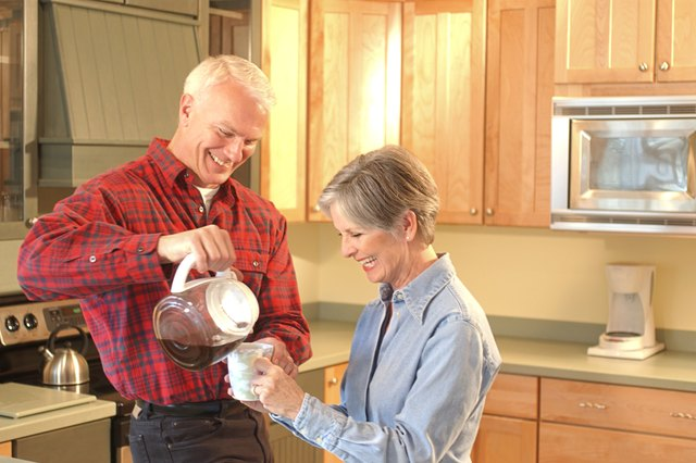 Man pouring coffee for woman