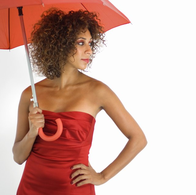 Woman in red dress under red umbrella