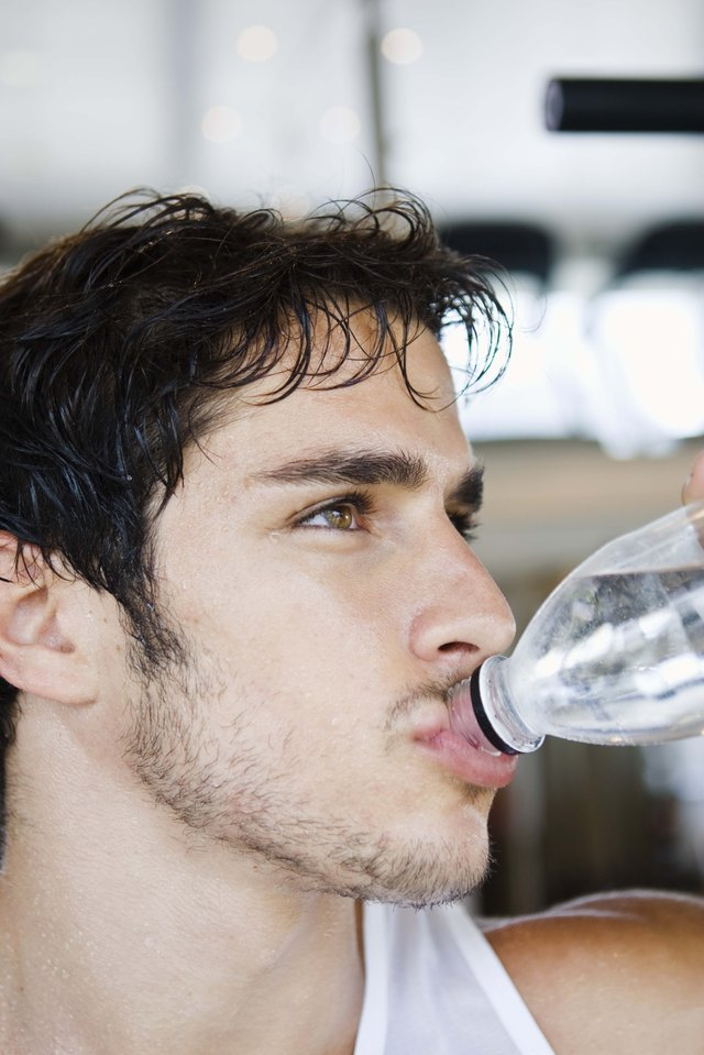 Man drinking bottle of water after workout