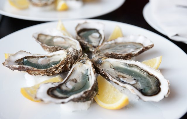 Fresh oysters on plate with lemon