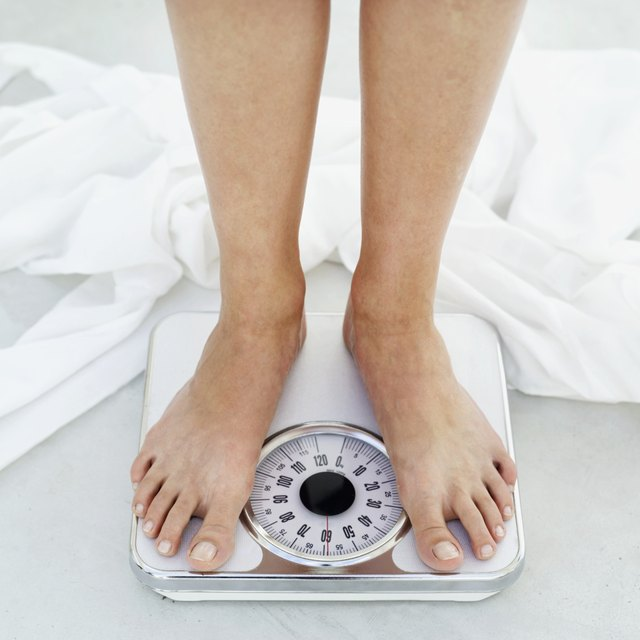 low section view of a person standing on a bathroom scale