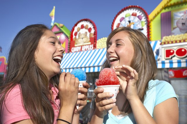 Girls eating snow cones at carnival