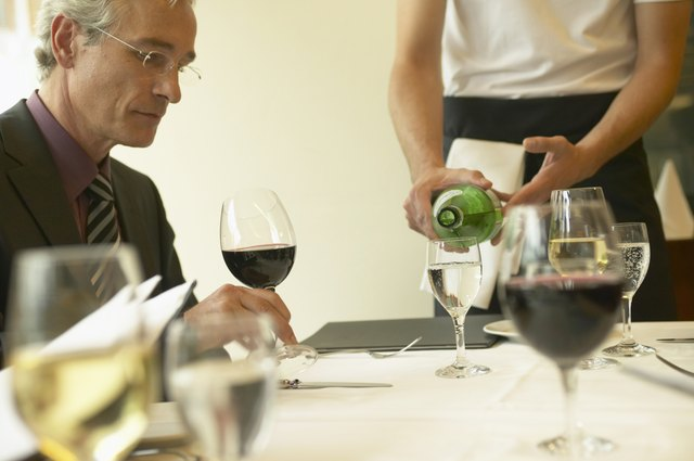 Waiter pouring glass of wine by businessman at restaurant table