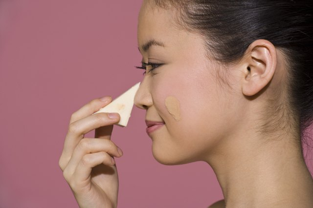 Woman applying makeup foundation
