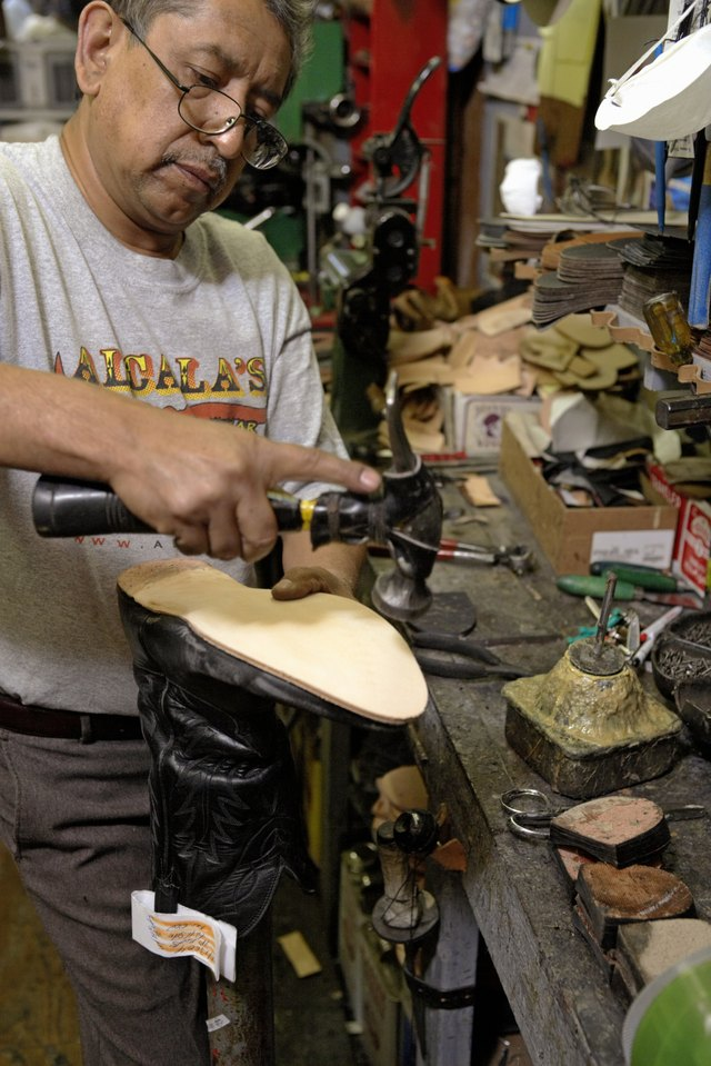 Cobbler working on sole of cowboy boot in workshop