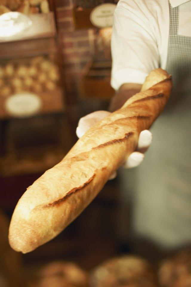 Bakery worker holding baguette
