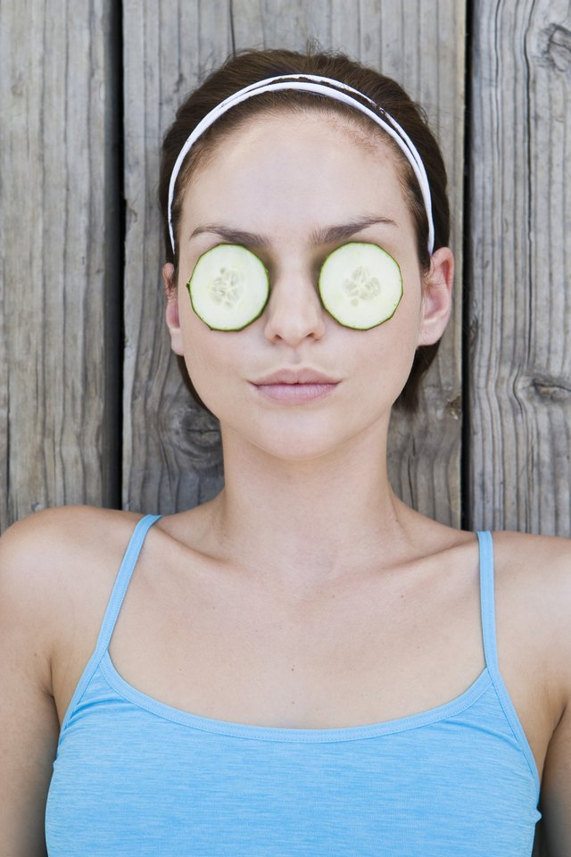 Woman relaxing with cucumber slices covering eyes