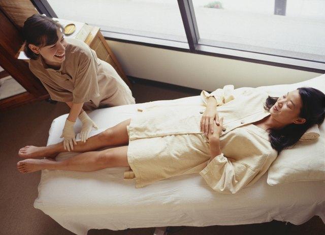 Woman lying on treatment table having leg wax