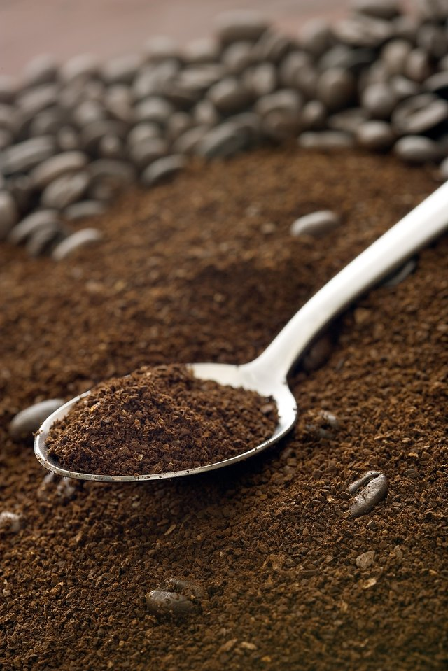 Spoon in ground coffee and whole beans
