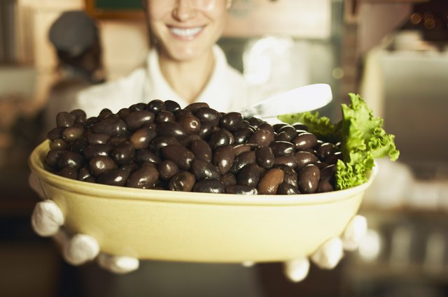 Close-up of woman holding bowl of black olives