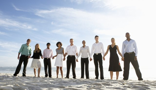 Nine businessmen and women holding hands on beach, portrait