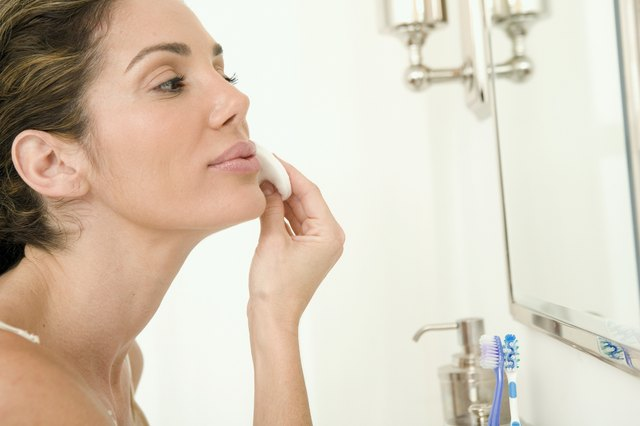 Mid adult woman wiping her face with a cotton pad
