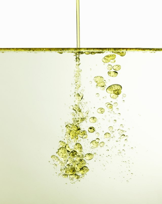 Oil being poured into water, studio shot