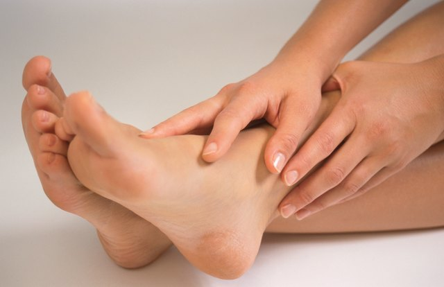 Close-up of person's hands on feet