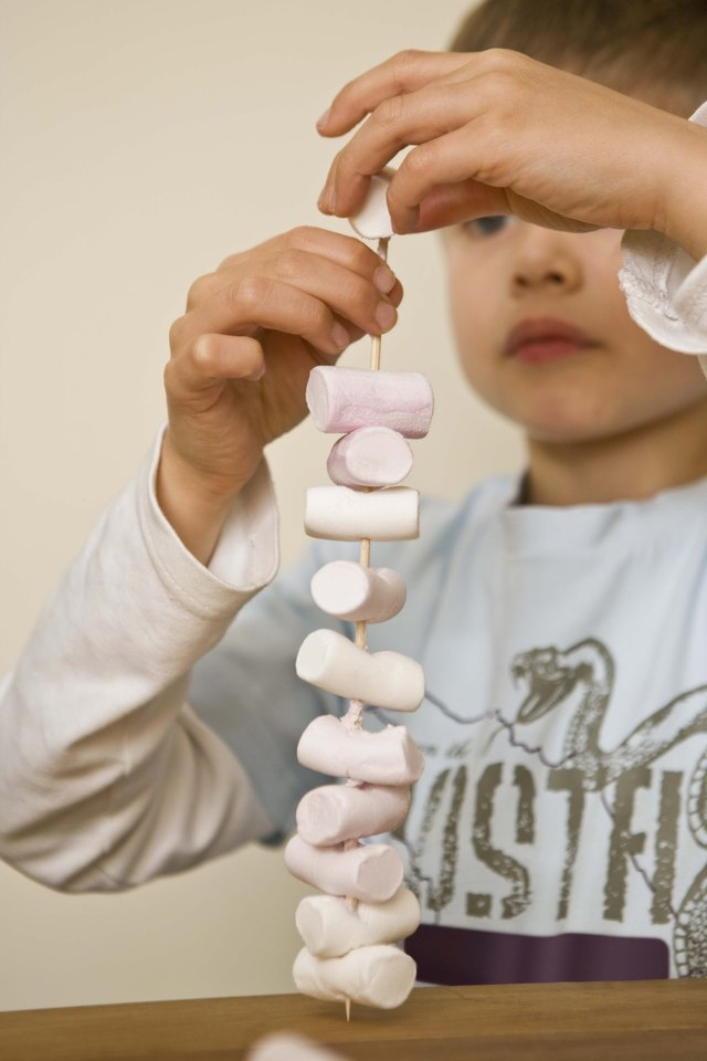 Boy putting marshmallows on skewer