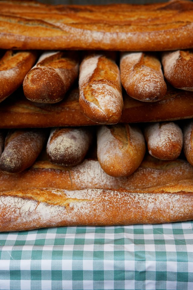 Baguettes stacked together on market stall, close-up