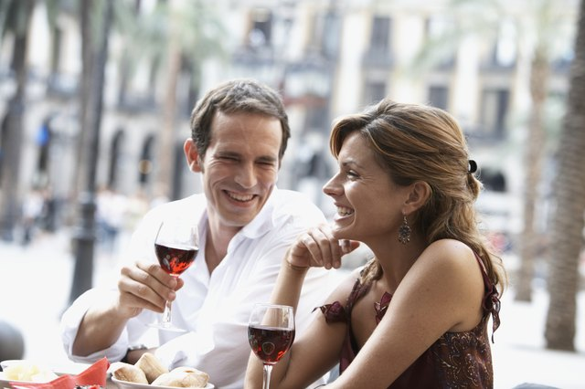 Spain, Barcelona, Placa Real, couple drinking wine at outdoor cafe
