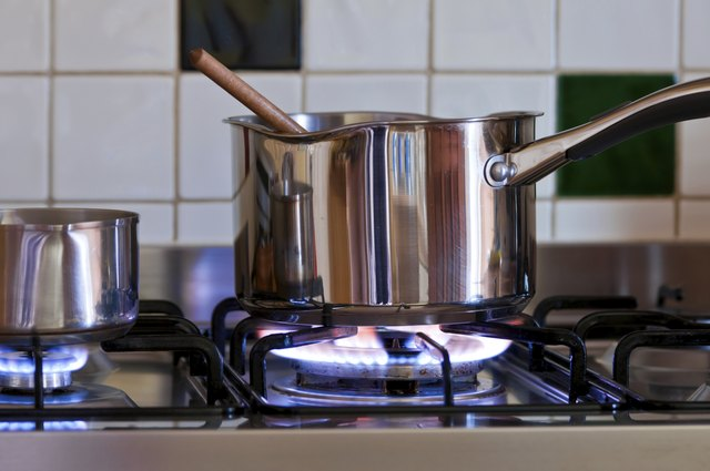 pan and wooden spoon on gas hob