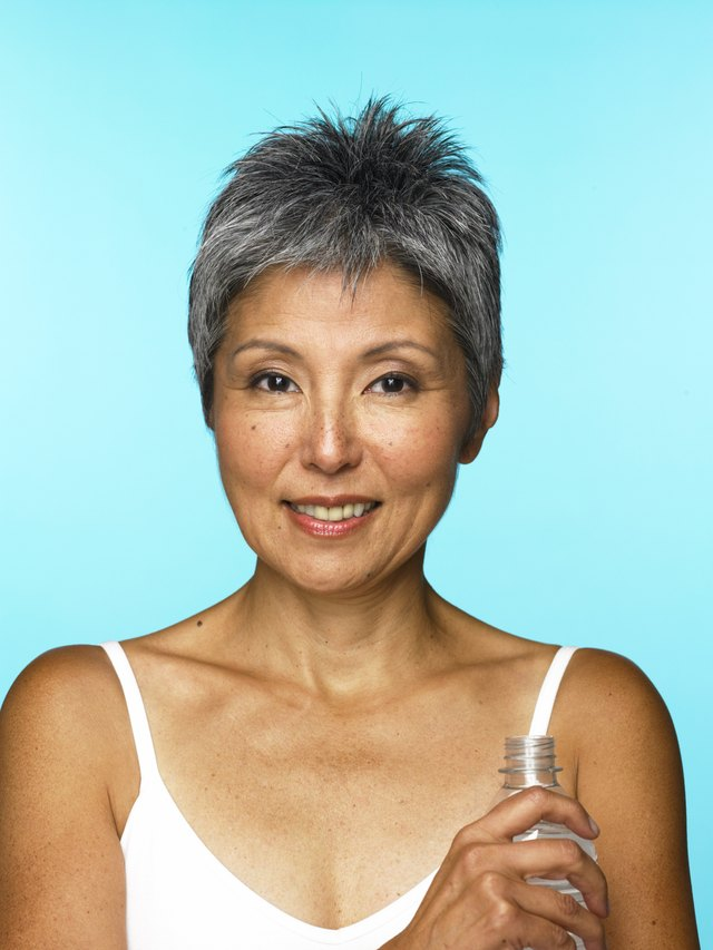 Mature woman holding water bottle
