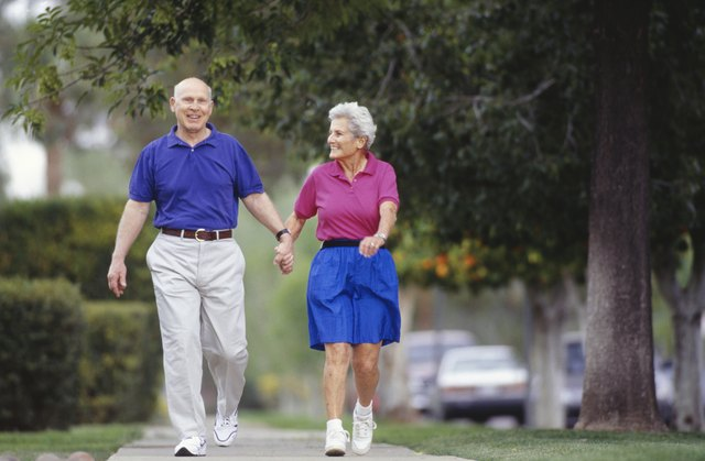 Senior couple walking side by side on sidewalk