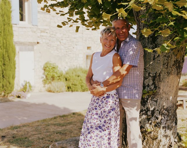 Couple embracing against tree by house, smiling, portrait