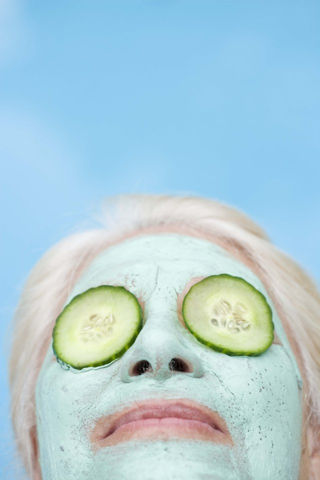 Woman in mud mask with cucumbers covering eyes