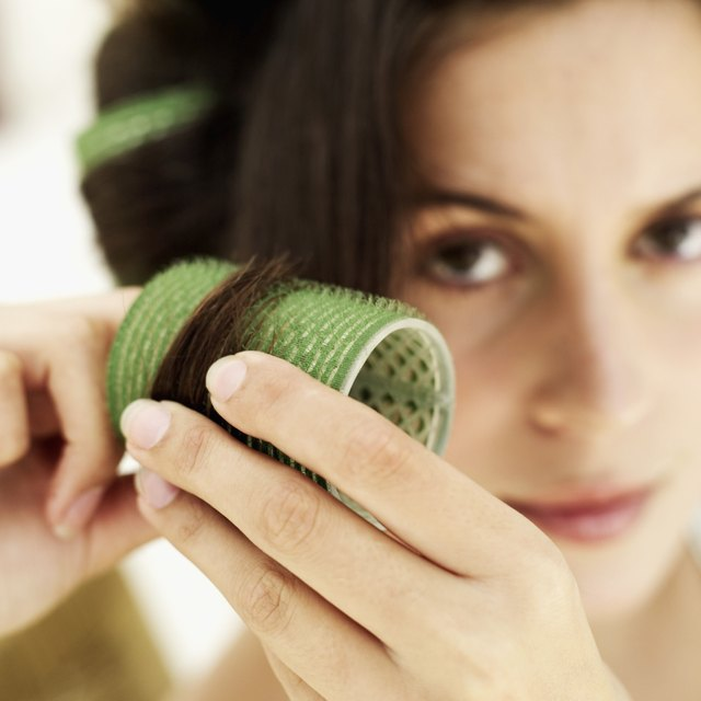close-up of a young woman putting on a curler