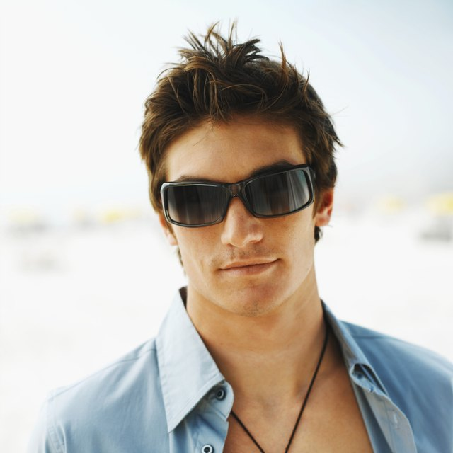 Front view portrait of young man smiling and wearing sunglasses