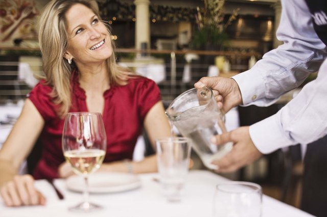 Server pouring water for woman