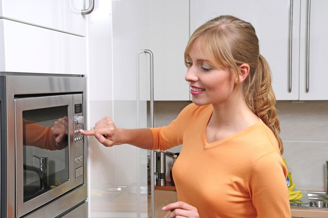 blond woman using a microwave for cooking