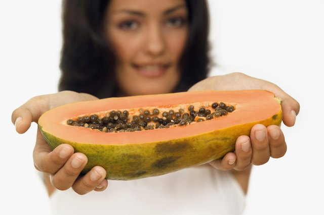 Portrait of a young woman holding out half a papaya