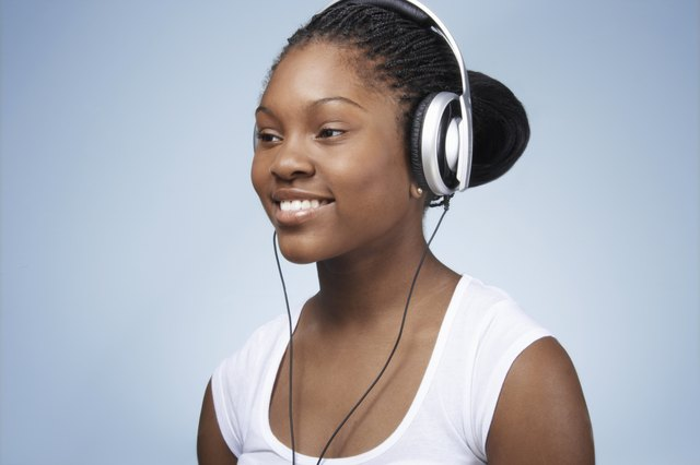 Teenage girl (15-17) listening to headphones, smiling, close-up