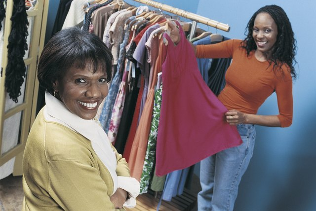 Shop Assistant Showing a Smiling Woman Dresses From a Clothes Rail in a Clothing Shop