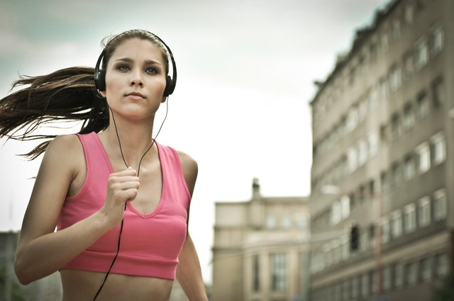 Young person listening misic running in city street