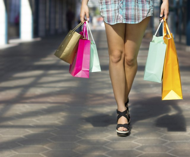 Beautiful women legs and colorful shopping bags at mall