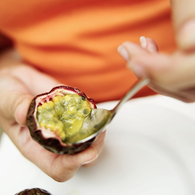 Close-up of a woman's hands scooping the inside of passion fruit