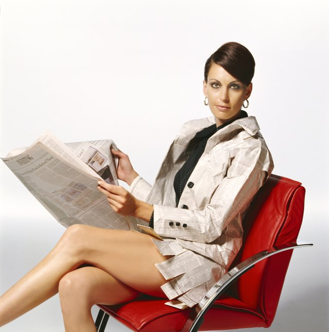 Woman Wearing Paper Clothing Sitting on a Red Leather Chair and Holding a Newspaper