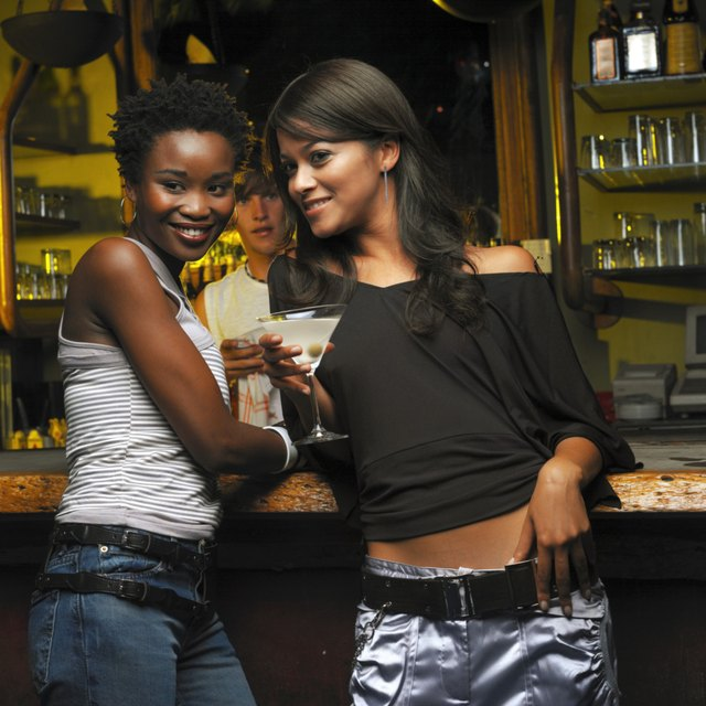 portrait of two young women standing at the bar counter holding drinks