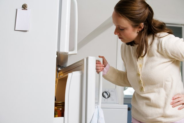 Woman opening refrigerator in kitchen at home