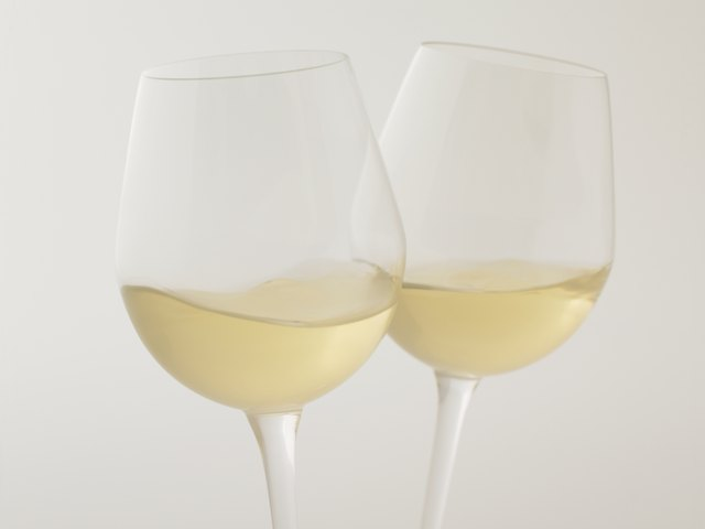 Glasses of white wine, close up, white background