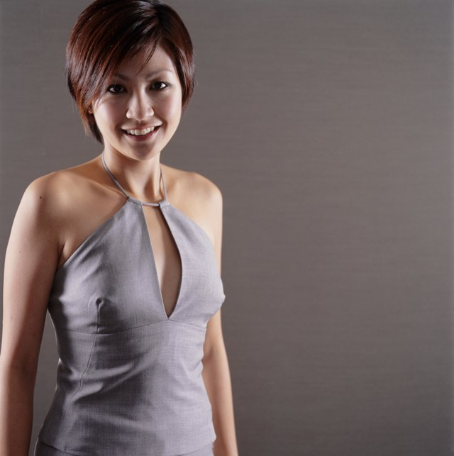 Young woman with short brown hair indoors wearing evening dress