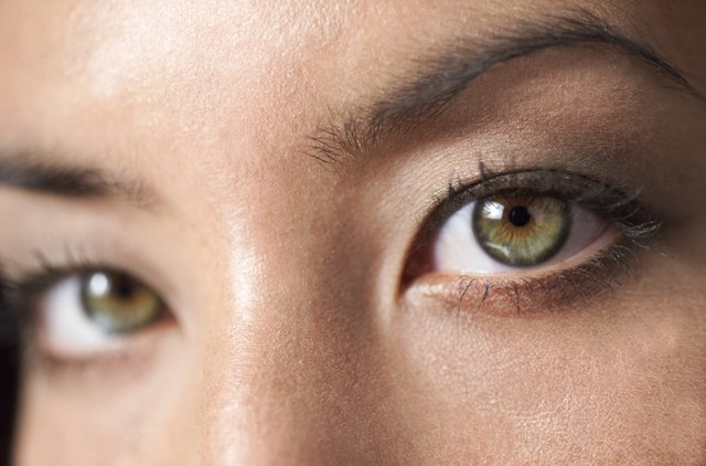 a close up shot of a the beautiful green eyes of a young attractive ethnic girl