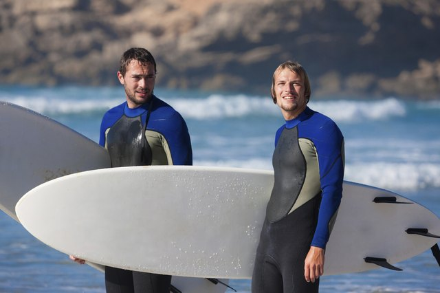 Two surfers talking on the beach
