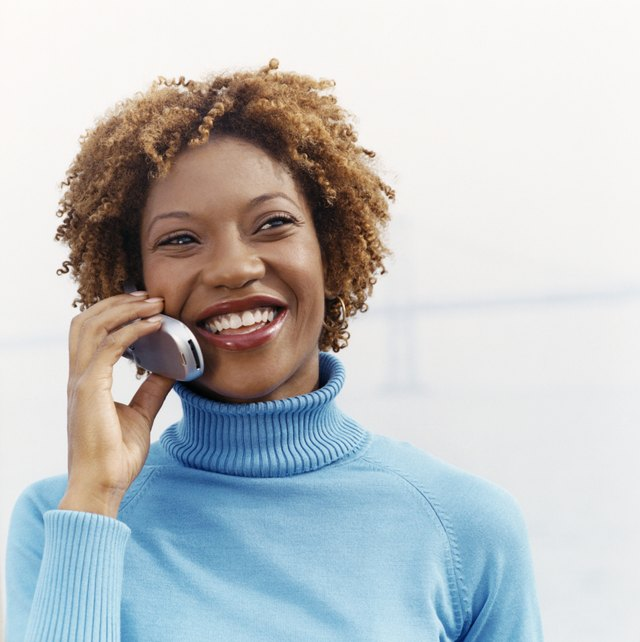 Woman Stands in a Polo-Neck Jumper, Smiling and Holding a Mobile Phone