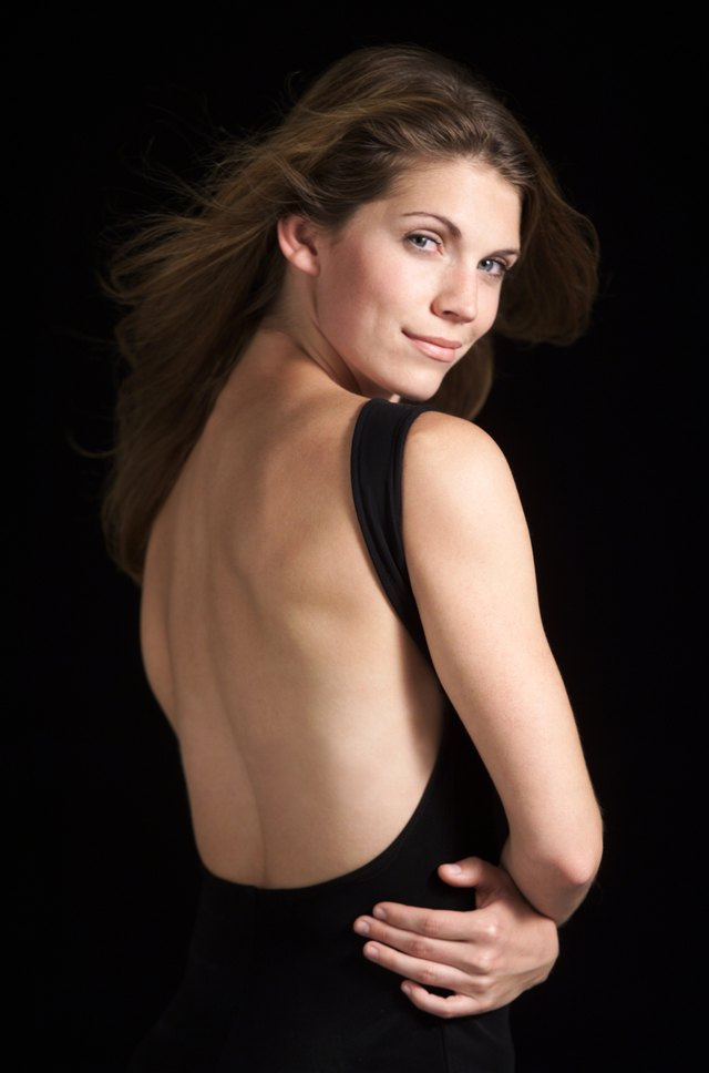a portrait of a beautiful caucasian woman in black backless dress folding her arms turns around and looks at camera while her hair flows in the wind