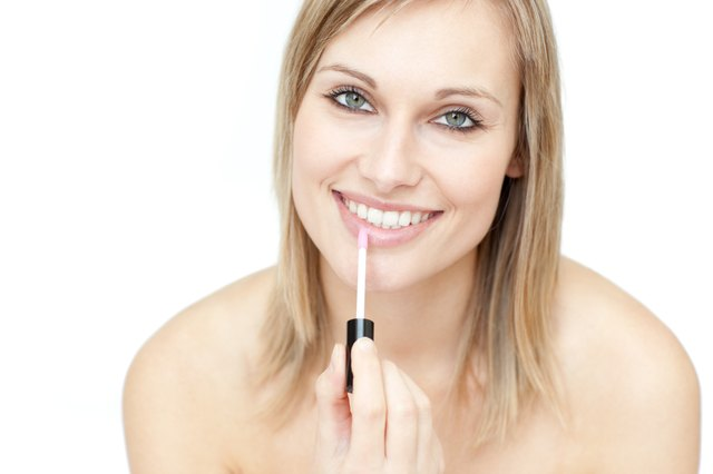 Attractive woman putting gloss