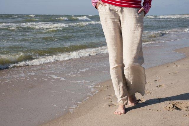 Woman in linen pants walking on the sea